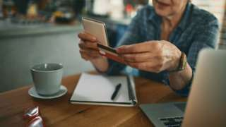 Woman at laptop with credit card and phone