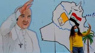 Woman in Baghdad takes selfie with Pope mural