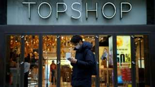 Man standing outside Topshop wearing face mask