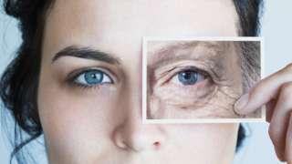 Mulher com foto de olho mais velho diante do rosto
