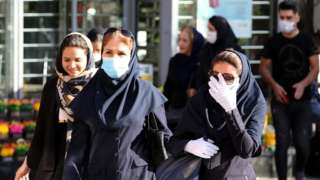 Iranian women wearing face masks and protective gloves walk in a street, in Tehran, Iran, 14 June 2020