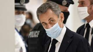 Image shows former French president Nicolas Sarkozy arriving for the opening hearing of his trial