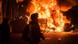 Un manifestante delante de un contenedor de basura en llamas.