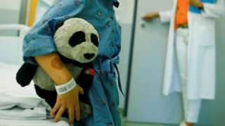 Child with soft panda toy in hospital