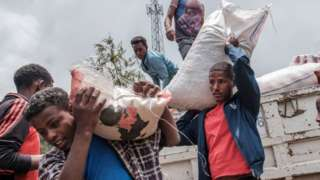 Civilians displaced by fighting in northern Ethiopia off load food and supplies from a truck, provided by the local population, at the Addis Fana School where they are temporary sheltered, in the city of Dessie, Ethiopia, on August 23, 2021