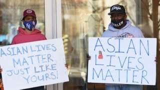 """شخصان يحملان لافتتين""""حياة الآسيوي مهمة"""" في الولايات المتحدة"""