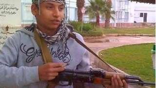 Khairi Saadallah holding gun in Libya