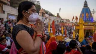 A devotee wearing protective face mask attends an evening prayer on the banks of Ganges river during Kumbh Mela, or the Pitcher Festival, amidst the spread of the coronavirus disease (COVID-19), in Haridwar, India, April 10, 2021.
