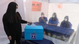Woman demonstrates casting her vote at a Central Election Commission event in Shoham, Israel (23/02/21)