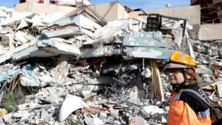 A member of emergency services stands next to a collapsed building in the Albanian town of Durres