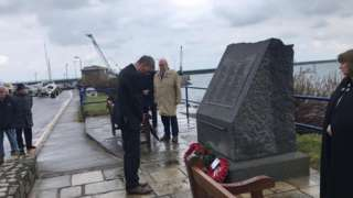 Kevin Gentle laying a wreath in front of Alfderney memorial