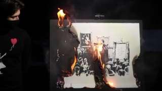 Screenshot from video of Banksy art being burnt