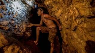 El Callao'daki La Culebra altında madeninde 1 Mart 2017'de çekilen bu fotoğrafta bir çocuk altın madeni arıyor.