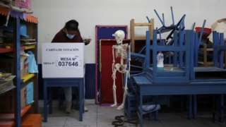 A voter casts a ballot at polling station set up in a school in Lima, Peru. Photo: 6 June 2021