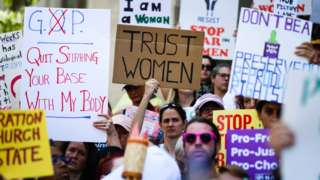 Women hold signs during a protest against a new abortion law in Atlanta on 21 May