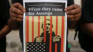 A protester showing Assange behind bars with: 'First they came for Assange'