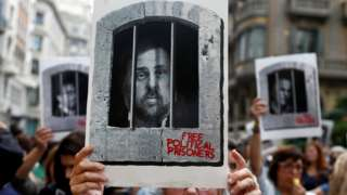 A protester shows a photo of Catalan former vice-president Oriol Junqueras behind bars as hundreds of people block the central Via Laietana in Barcelona, Spain, 14 October 2019