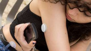A woman using the flash glucose monitoring system