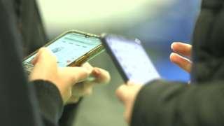 Two teens hands holding smartphones