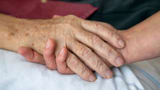 An older holds hands with a younger person