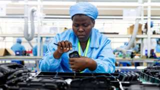 Ugandan factory workers assemble mobile phone cases