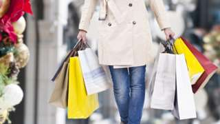 Woman holding shopping bags in a Christmassy high street