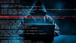 Generic cyber attack image showing hooded hacker at laptop, overlayed with code