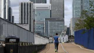 A jogger runs through a quiet Canary Wharf
