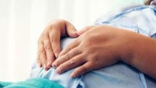 ผู้หญิงท้องเอามือจับท้อง