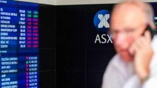 Man in front of ASX market board.