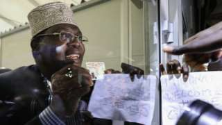 Mr Miguna holds his identification up to glass after being detained earlier this week in airport