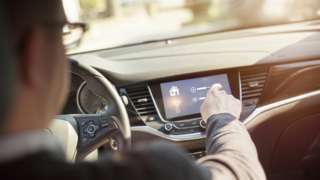 A man interacts with the screen in his connected car