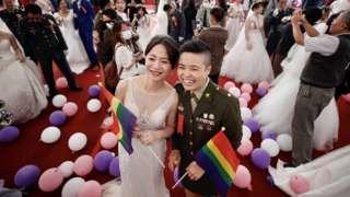 Couple Yi Wang (R) and Yumi Meng (L) react during a military mass wedding in Taoyuan, Taiwan, 30 October 2020