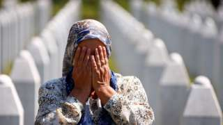 A woman prays at a graveyard, ahead of a mass funeral in Potocari near Srebrenica on Saturday