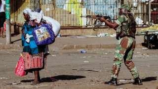 A vendor scurries for cover with her wares as soldiers disperse demonstrators on August 1 2018, in Harare, Zimbabwe