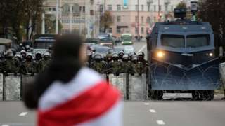 A protester with a flag stands in front of Belarusian policemen and a water cannon that block a road during a rally against government and President Lukashenko in Minsk, Belarus, 25 October 2020