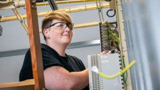 A female Openreach engineer working in a telephone exchange