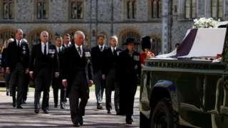 Aelodau o'r Teulu Brenhinol yn cerdded tu ôl i arch Dug Caeredin ar dir Castell Windsor