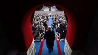 Trump walks through the doorway to the inauguration podium