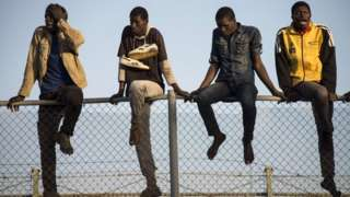 Four African migrant men sit on a mesh boarder fence separating Morocco from the Spanish enclave of Melilla