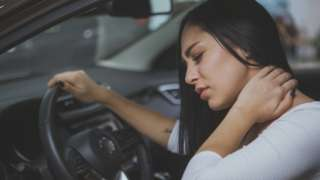 A woman rubbing her neck after experiencing a whiplash injury in a car