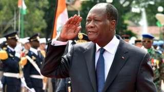 Alassane Ouattara exécutant le salut militaire lors de la fête de l'indépendance.
