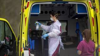 Worker wearing protective clothing cleans ambulance