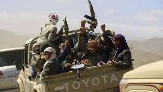 Armed Yemeni men raise their weapons as they gather near the capital Sanaa