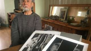 Humberto Gattica with some of his pictures