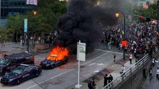 A police car burns in Atlanta, Georgia, as people protest against the death in Minneapolis police custody of African-American man George Floyd
