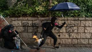 A masked protester - not the 12-year-old boy - holding an umbrella in one hand and a Molotov cocktail in the other