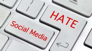 Composite image of a keyboard with words hate and social media superimposed