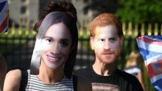 People pose for a picture in Prince Harry and Meghan Markle masks