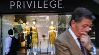 Homem engravatado passa em frente a vitrine de loja com nome 'Privilege'